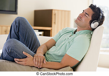 Man in living room listening to headphones sleeping