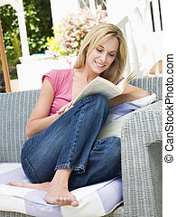 Woman sitting outdoors on patio with book smiling