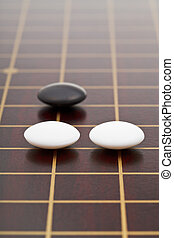 three stones during go game playing on wooden board close up