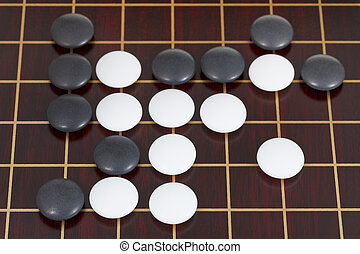 top view of many black and white go game stones - top view...
