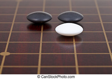 three stones during go game playing on goban close up