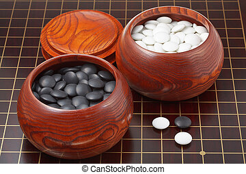 go game stones and wooden bowls on wood board - black and...