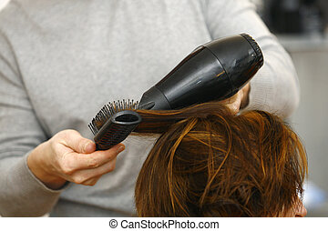 stylist drying woman hair in hairdresser salon