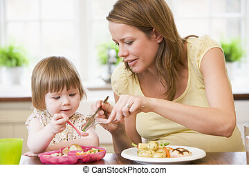 Pregnant mother in kitchen eating chicken and vegetables...