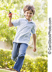 Young boy with toy airplane running outdoors smiling