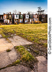 Cracked sidewalk and abandoned row houses in Baltimore, Maryland.