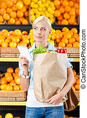 Girl hands paper bag with fresh vegetables reading list of products