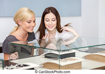 Two girls looking at glass case with jewelry at jeweler's...
