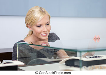 Close up of girl looking at jewelry in glass case at...