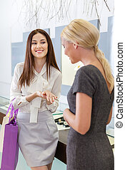 Two ladies discuss purchases and engagement ring at...