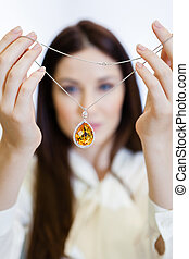 Woman holding necklace with yellow sapphire at jewelers shop...