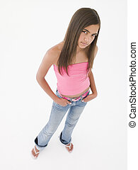 Young girl standing with hands in pockets frowning