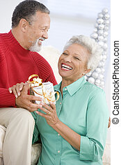 Senior Couple Exchanging A Christmas Gift