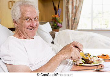 Senior Man Eating Hospital Food In Bad