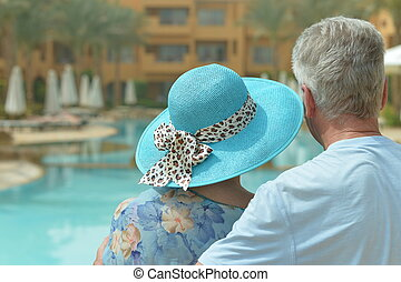 Elderly couple at pool - Back view elderly couple standing...