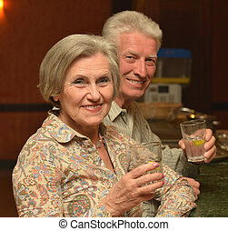 Senior couple drinking cocktail - Happy elderly couple...