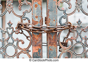 Rusting gate locked with chain - An old wrought iron gate...