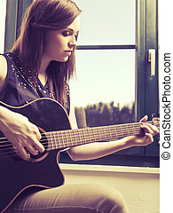 Playing acoustic guitar by the window - Photo of a woman...