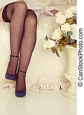 legs on bed with fishnet stockings and heel shoes
