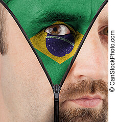Unzipping face to flag of Brazil - close-up of a face...