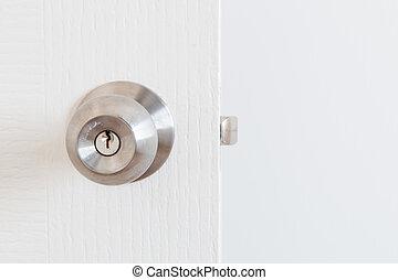 Detail of a metallic knob on white door , tainless steel...