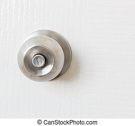 Detail of a metallic knob on white door , tainless steel...