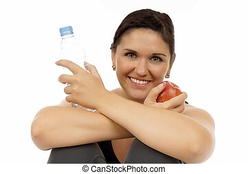 healthy living - young woman with an apple and water bottle
