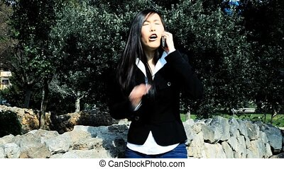 Angry asian business woman on the phone screaming