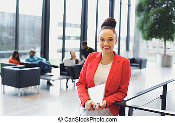 Pretty young businesswoman in office with laptop in hand