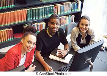 Confident young students at library using computer - Diverse...