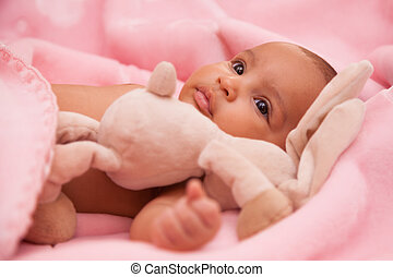 Adorable little african american baby girl playing with a...
