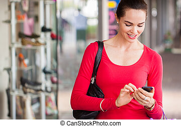 Happy woman texting on mobile phone