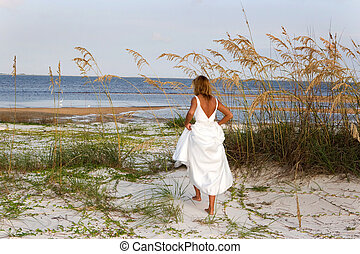 Bride In Sea Oats - A woman in a bridal gown walks through...