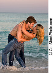 Couple Embrace In The Surf - A young couple wearing...