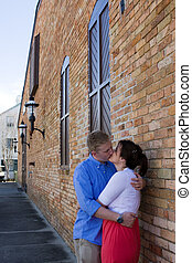 Couple Kissing By Brick Building