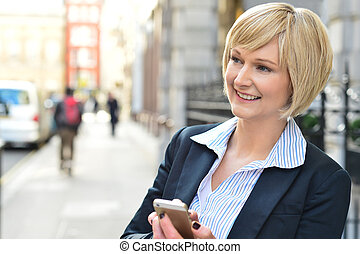 Corporate woman operating her cellphone - Businesswoman...