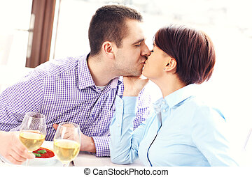 Kissing couple in a restaurant - A picture of a young couple...