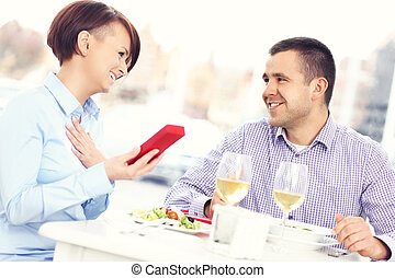 Beautiful woman with present in a restaurant