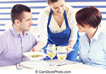 Couple being served in a restaurant - A picture of a young...