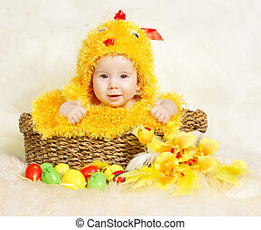 Baby in Easter basket with eggs in chicken costume. Easter holiday concept: nest with baby chick