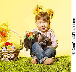 Easter little girl, kid holding bunny rabbit basket eggs...