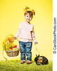 Easter little girl, small kid with bunny rabbit basket eggs over yellow background