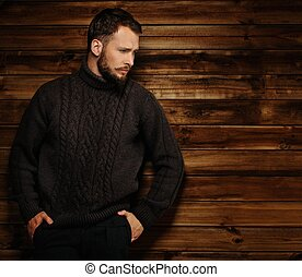 Handsome man wearing cardigan in wooden rural house interior...
