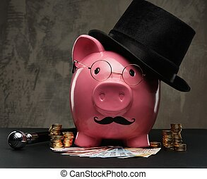 Piggybank in glasses and hat with pile of coins and...