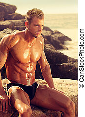 Muscular man - Musucular young man sitting on rocks at the...