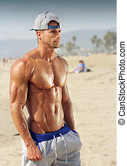 Bodybuilder on beach - Handsome young muscular male model on...