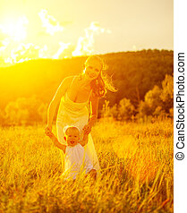 happy family on nature outdoors mother and baby daughter doing first steps at sunset