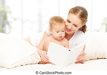 Mother reading book baby in bed before going to sleep -...