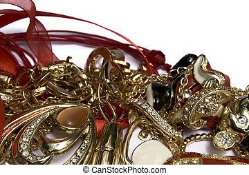Heap of jewelry gold, jewels, a red tape, on a white...