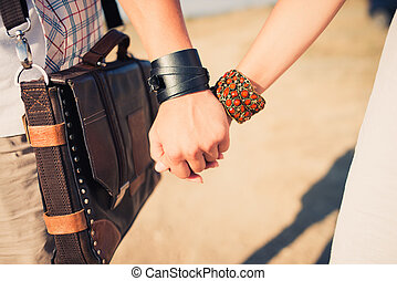 young couple holding hands - Close-up image of a young...